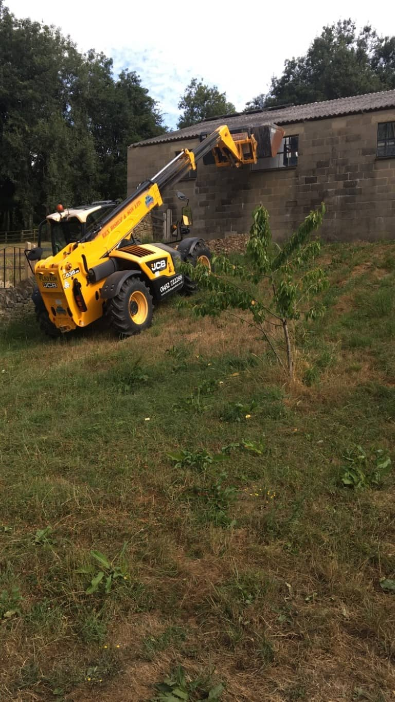 Digger going up a slight hill to an abandoned barn