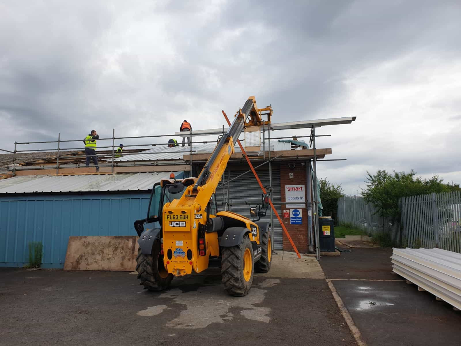 Machinery demolishing a roof that also has scaffolding on it