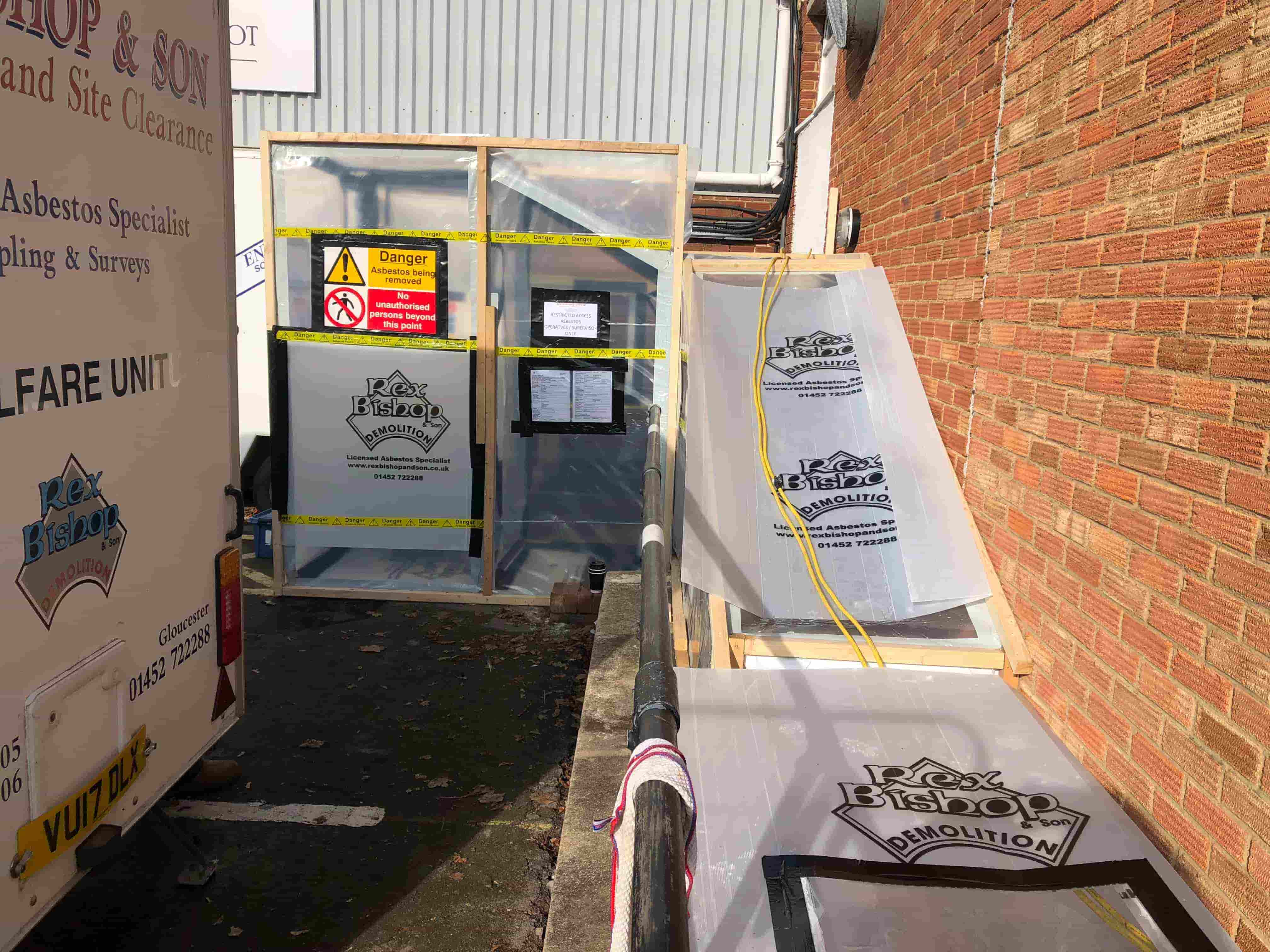 Asbestos removal tent with warning signs outside of the side of a building
