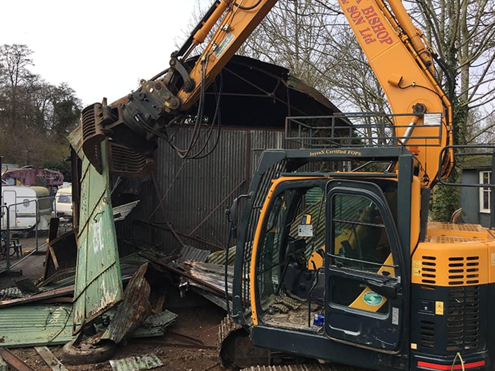 Digger demolishing an abandoned barn