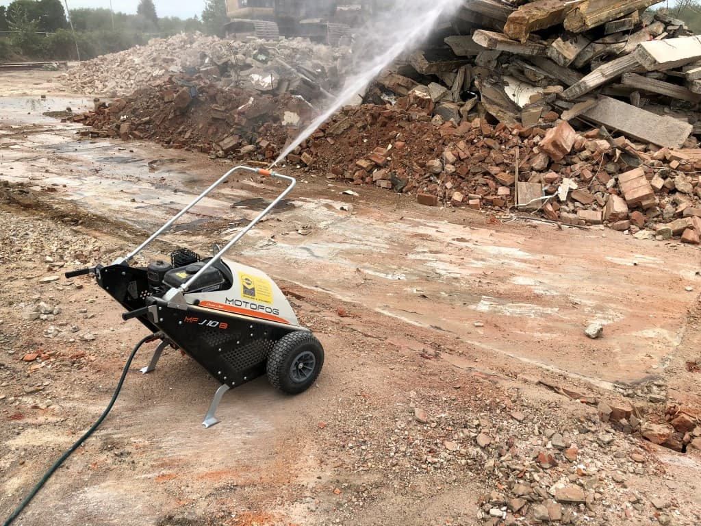 Machine spraying a stream of water over a pile of rubble