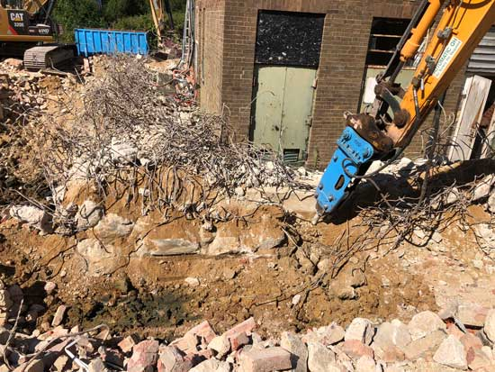Machine breaking up bricks into rubble