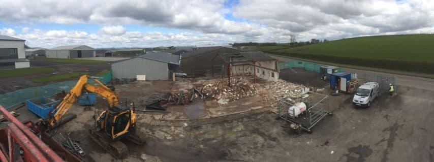 Digger carrying out a site clearance in front of a hangar with a pile of rubble behind the digger on the ground