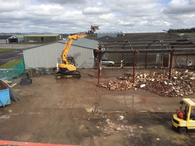 Digger demolishing the roof of a building