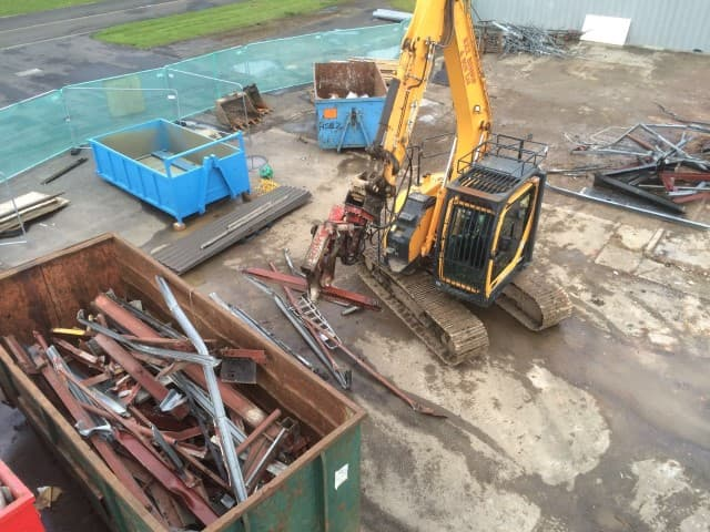 Digger lifting rubble into a container