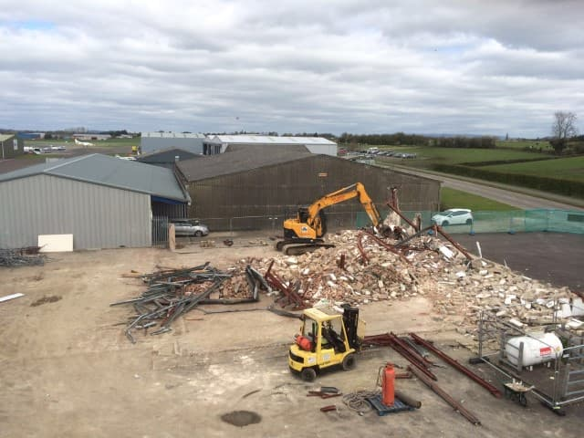 Diggers carrying out a site clearance in front of a hangar with a pile of rubble in front of them