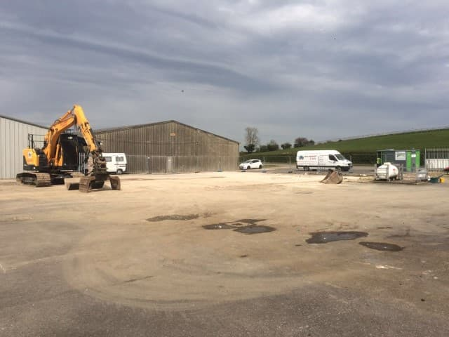 Digger in front of a hangar with two vans in view