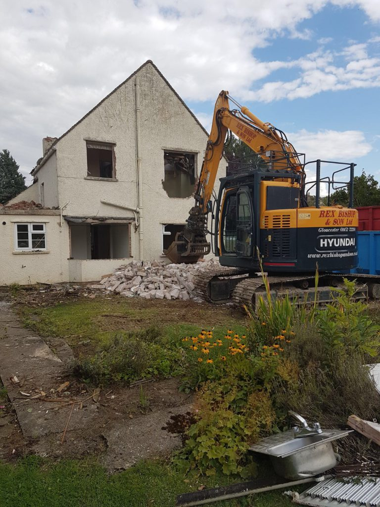 Digger in front of an abandoned house