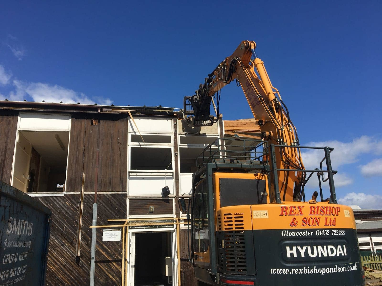Digger ripping down the roof outside of the moat school building