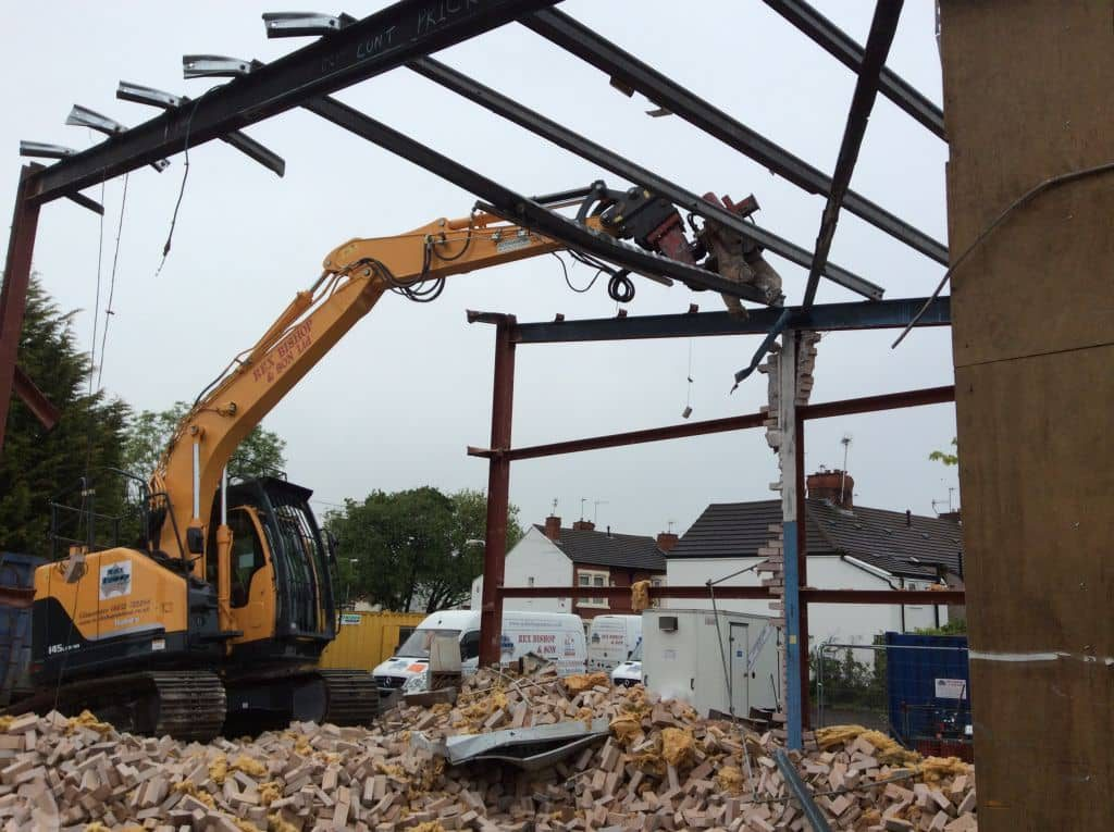 Digger on a pile of rubble tearing a roof down