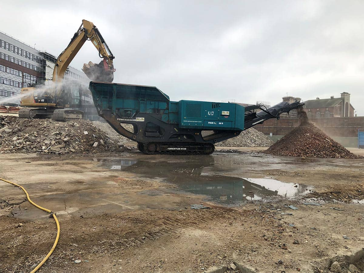 Digger filling up a green container with rubble